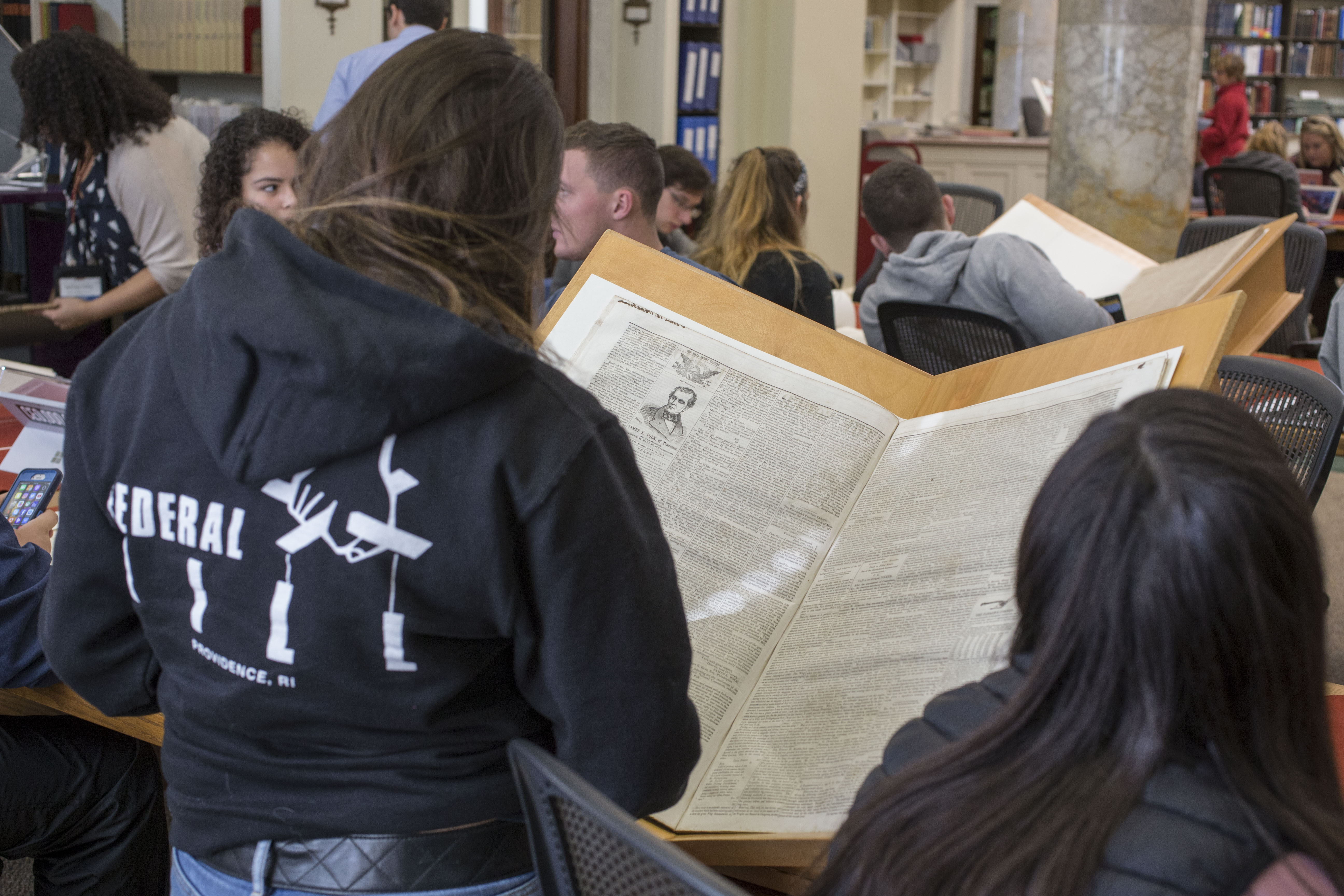 seminar participants examining a nineteenth-century newspaper