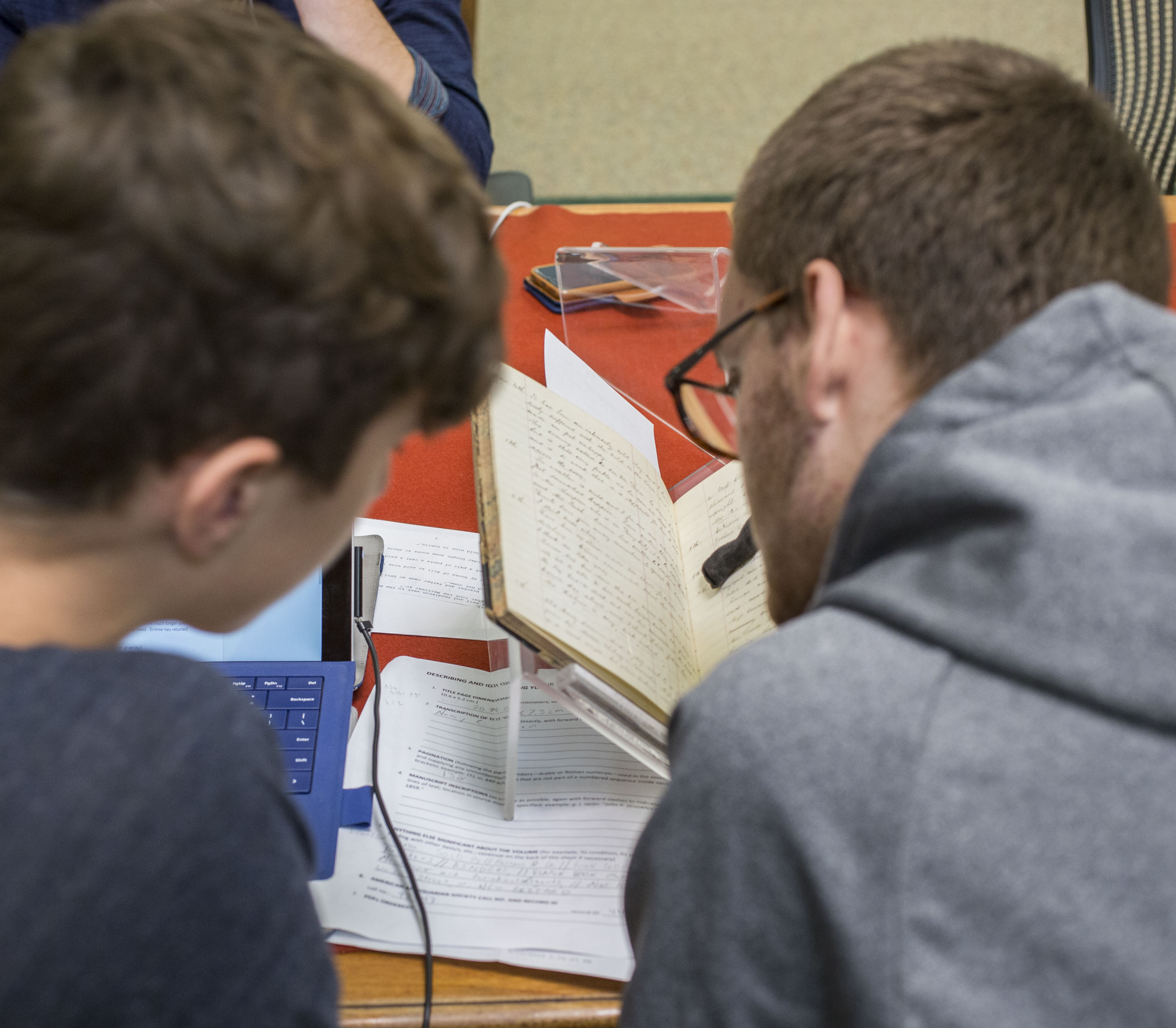 two seminar participants looking at a primary source in a cradle